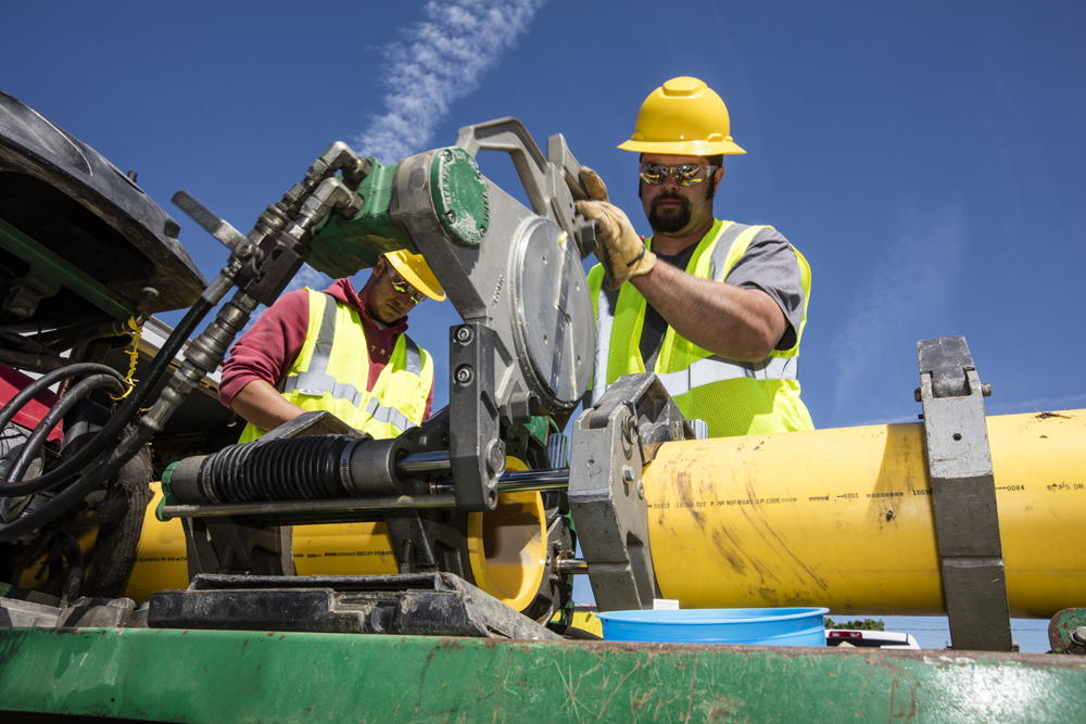 Laborers cutting a pipe