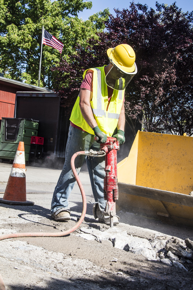 Laborer using jack hammer to break up cement