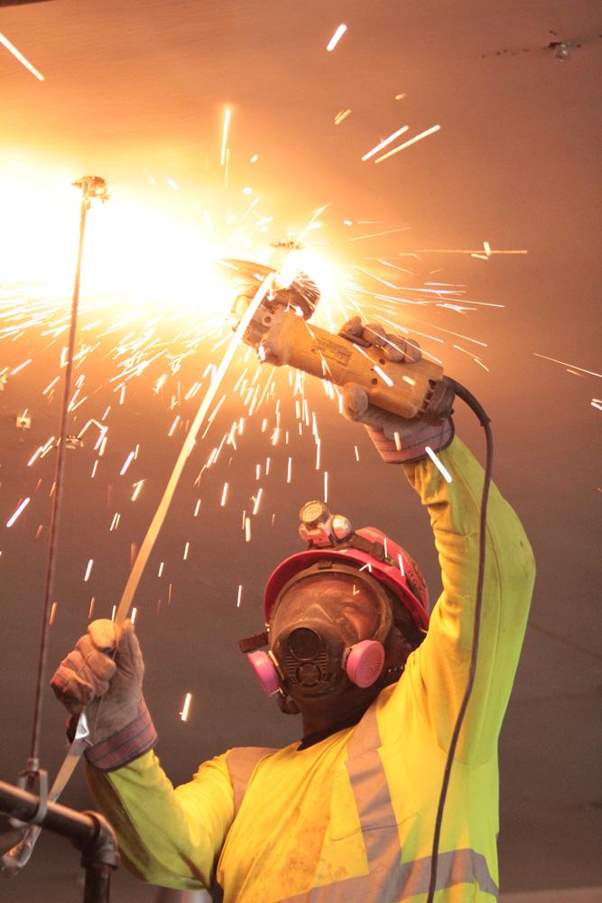 Laborer cutting a piece of metal - demolition work